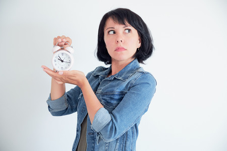 Surprised young woman with clock wondering eyes. stressed concept