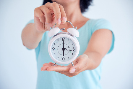 Little blue alarm clock in the hands of woman, the concept of saving time Stock Photo