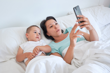 mom and baby lie together in bed and take selfies