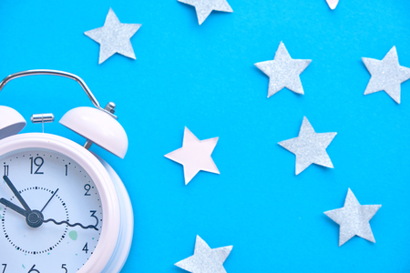 Time for party and wake up to work, white alarm clock with party decoration light bokeh in the red background before midnight. Stock Photo