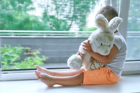 boy of two years sitting by the window and hugs a toy Bunny. rainy weather, waiting for dad to come home from work Archivio Fotografico