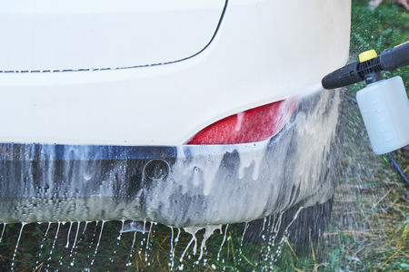 Shot of a man washing his car under high pressure water outdoors.