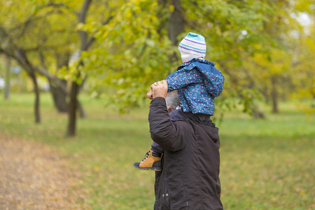 Happy weekend concept. happy grandfather and grandson are walking in the park. Autumn day. Grandpa rolls on the shoulders of a little boy. Standard-Bild