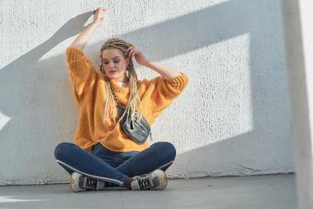 a woman with african pigtails is sitting on the floor. Waist bag on the shoulder, blonde with African braids.