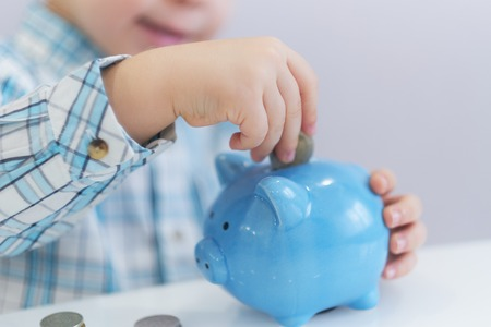 three years old boy puts money in a piggy bank, piggybank concept. mantesori space in the house Zdjęcie Seryjne
