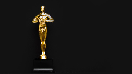 gold statue trophy on a yellow background, symbol of the victory of the actor in his profession. Archivio Fotografico