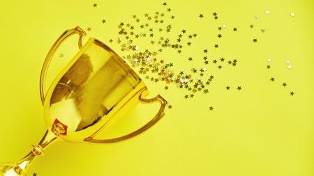 Champion-Gold-Cup-Trophäe auf gelbem Hintergrund. Minimalismus-Stil, Siegesfeier-Konzept. und goldene Konfettisterne sind verstreut Standard-Bild