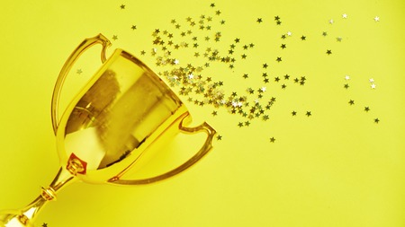 Champion gold cup trophy on yellow background. minimalism style, victory celebration concept. and golden stars of confetti are scattered around Stock fotó