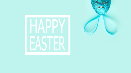 one easter egg on a turquoise background, with bunny ears. minimalism concept Stock Photo