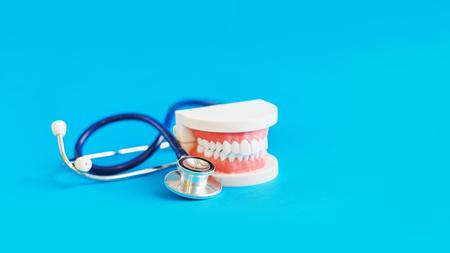 Modell mit weißen Zähnen und Stakescope auf blauem Hintergrund. Zahnpflege. Konzept der vorbeugenden Untersuchung der Mundhöhle. Standard-Bild