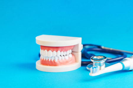 White teeth model and stakescope on blue background. teeth care. concept of preventive examination of the oral cavity.