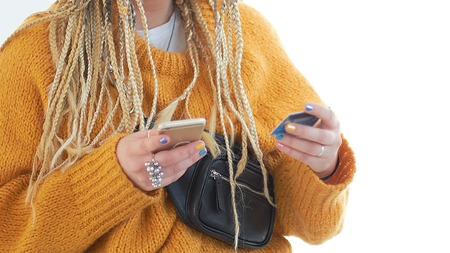 Extravagant plus size young woman with glasses holding a smartphone and a credit card in her hands. pays for purchases online