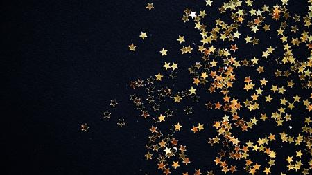 Golden Christmas stars on black background.