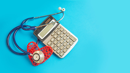 red heart and calculator with stethoscope isolated on blue background. tax offset concept. Medical Expense Deductions and Tax Breaks. affordable care act. high cost health care Banque d'images - 121347988