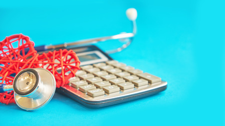 red heart and calculator with stethoscope isolated on blue background. tax offset concept. Medical Expense Deductions and Tax Breaks. affordable care act. high cost health care
