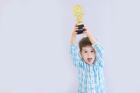 lustiger Junge im Alter von drei Jahren, der eine Trophäe hält