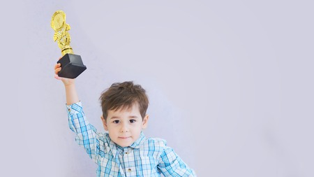 funny boy age three years old, holding in holding a trophy