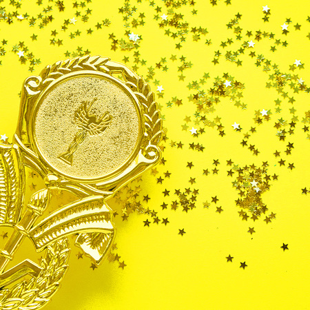 Champion gold cup trophy on yellow background. minimalism style, victory celebration concept. and golden stars of confetti are scattered around Stock Photo