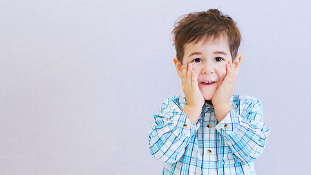 funny boy three years old hid his face in his hands. childhood fears. Stock Photo