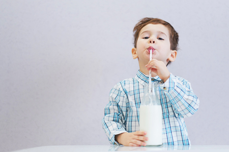 cute happy boy with dark eyes drinks milk from a bottle. the child is wearing a plaid shirt 版權商用圖片