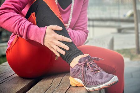running problem for athlete training outdoors. Runner sport knee injury. Athlete running clutching calf muscle after spraining it while out jogging on the beach near ocean Stock Photo - 125149010