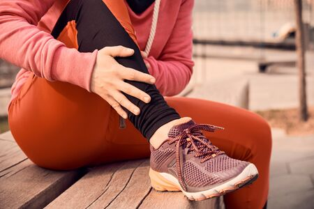 running problem for athlete training outdoors. Runner sport knee injury. Athlete running clutching calf muscle after spraining it while out jogging on the beach near ocean.