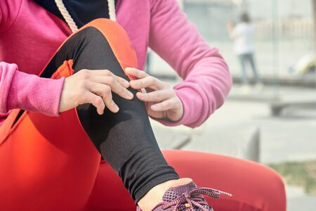 running problem for athlete training outdoors. Runner sport knee injury. Athlete running clutching calf muscle after spraining it while out jogging on the beach near ocean. Stock Photo - 125225499