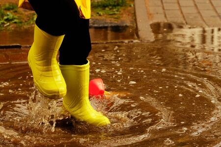 child jumps in a puddle arranges a storm for a small plastic boat. legs in yellow rubber boots