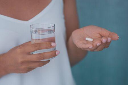 Mujer enferma que toma medicamentos, antidepresivos, analgésicos o antibióticos. Señora joven bebiendo anticonceptivos.