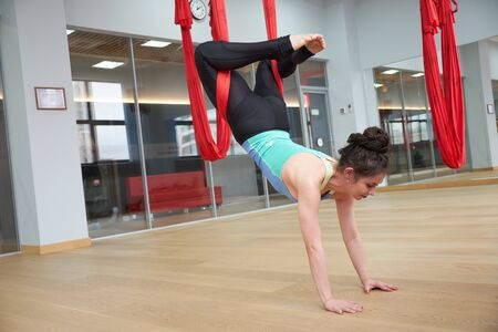 Adult woman practices aero anti-gravity yoga position in studio. Inversion bow pose in aero anti gravity yoga. Aerial exercises