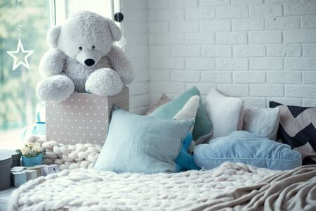 cozy childrens room in bright soft colors, pillows and a blanket are lying on the bed