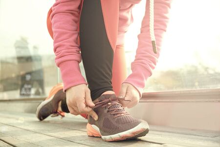 Mature fitness woman tie shoelaces on road. Cheerful runner sitting on floor on city streets wearing sport shoes. Active latin woman tying shoe lace before running. Reklamní fotografie