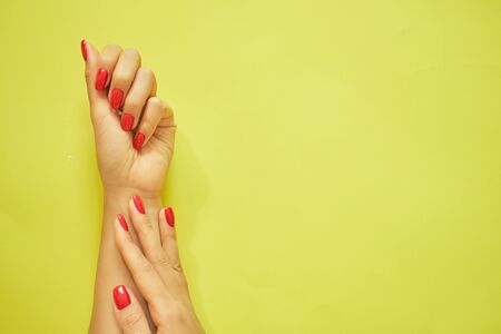 perfect red manicure. luxury nail and hand care in the salon. yellow background. Imagens