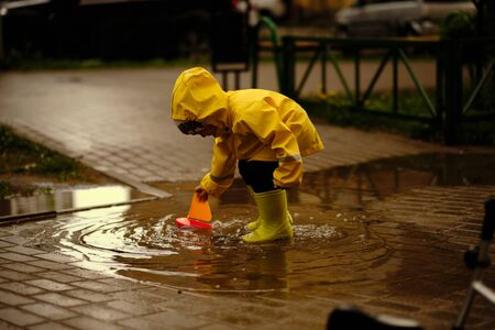happy child is playing in a puddle on a summer rainy day. a boy in a yellow raincoat walks in the park.