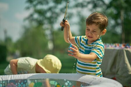 Happy Toddler boy playing in the fishing. hot summer day. children playing outside