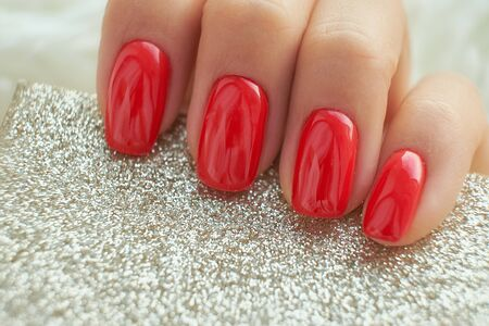perfect red manicure. nail and hand care in the salon.