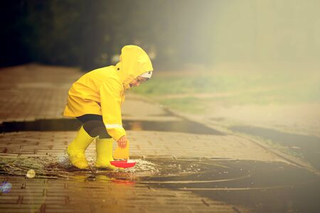 funny boy will save its plastic boat that sank in a puddle. a boy in a yellow raincoat walks in the park.
