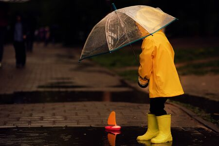 little boy plays with a plastic boat in a puddle on a rainy autumn day. Stock Photo