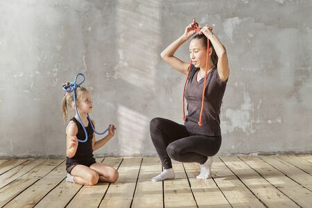 happy woman and little girl study in classroom. teacher and teacher in the dance class. individual sessions. teacher carefully helps to stretch the muscles