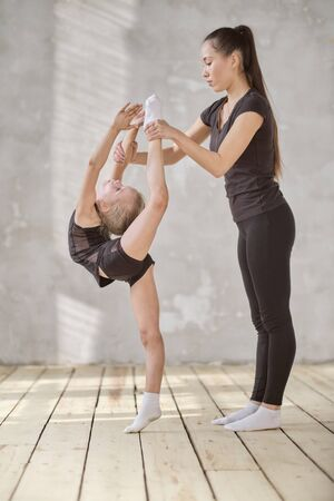 Cute flexible little balerina stretching legs with help of her teacher in ballet studio. teacher and student little girl do exercises together in dance class.