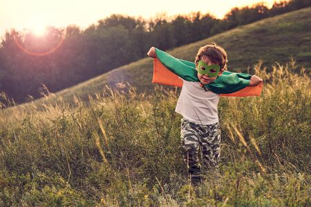 little boy playing a superhero. Kid in an Superheros costume. happy child runs to meet the photographer. Stock Photo