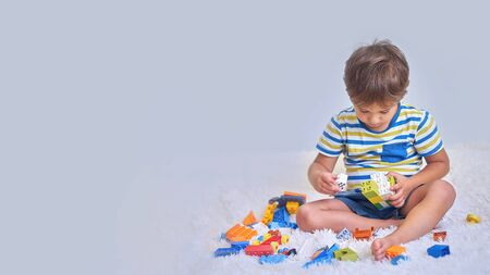 happy asian boy playing with colorful construction plastic blocks on white Bed at home. Imagens