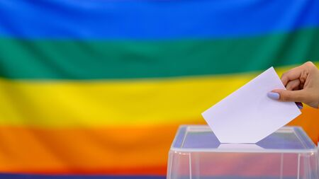 Hand holding ballot paper for election vote concept. elections, The hand of woman putting her vote in the ballot box. Rainbow flag on background. Banque d'images