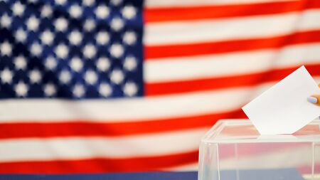 woman putting a ballot in a ballot box on election day. Close up of hand with white votes paper on usa flag background Reklamní fotografie