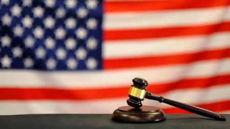Judge's gavel and over USA flag. Symbol for jurisdiction. Law concept a wooden judges gavel on table in a courtroom or law enforcement office on blue background. Copy space for text.