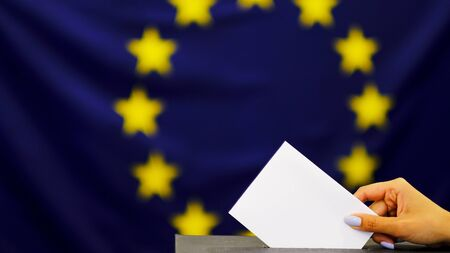 Hand holding ballot paper for election vote concept. elections, The hand of woman putting her vote in the ballot box. on European union flag background.