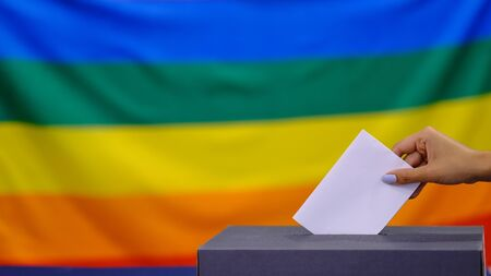 Hand holding ballot paper for election vote concept. elections, The hand of woman putting her vote in the ballot box. Rainbow flag on background. Stockfoto