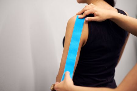 kinesiology taping treatment with blue tape on female patient injured arm. Sports injury kinesio treatment.