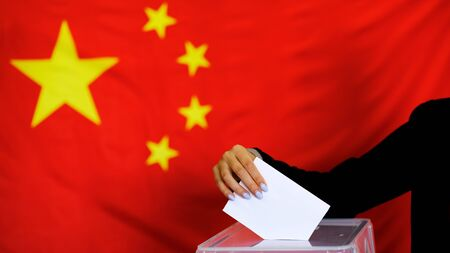 Hand holding ballot paper for election vote concept. elections, The hand of woman putting her vote in the ballot box. China Flag on background Foto de archivo