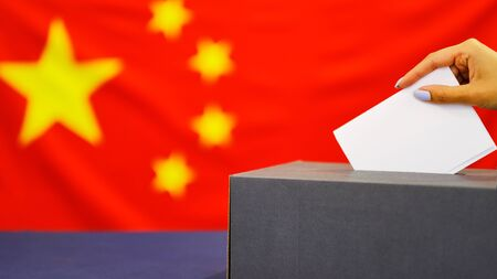 Hand holding ballot paper for election vote concept. elections, The hand of woman putting her vote in the ballot box. China Flag on background Banque d'images
